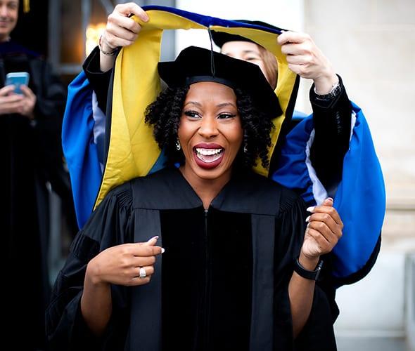Graduate receiving hood during ceremony