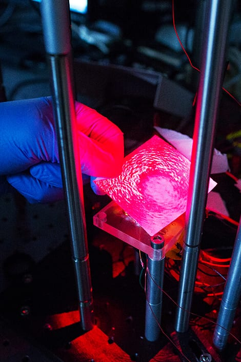A fushia laser is shot on a glass slide with blood that is coated with magnetic beads to reveal protein concentration.