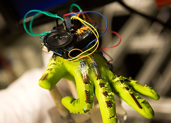A lime green gloved hand flexes fingers balancing a small computing system with various colored wires