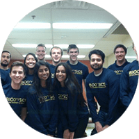 Students wearing biophysics shirts gather and smile for a picture