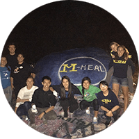 M-Heal members gather around the rock painted with the M-Heal emblem.
